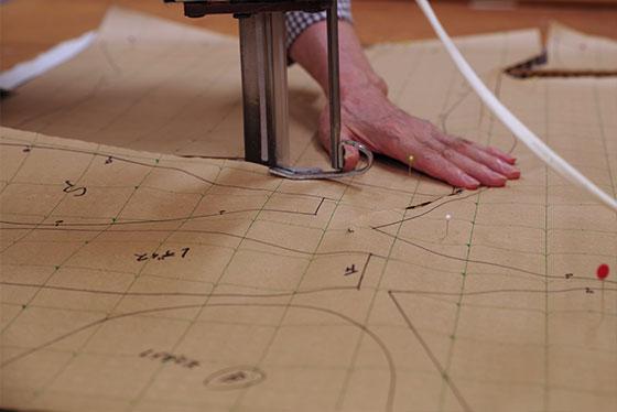 生地を無駄にしないようにレイアウトされた型紙を裁断機でカット