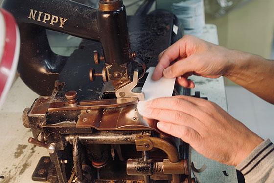 手でカットした革の断面を回転刃が機械で斜めにスライス